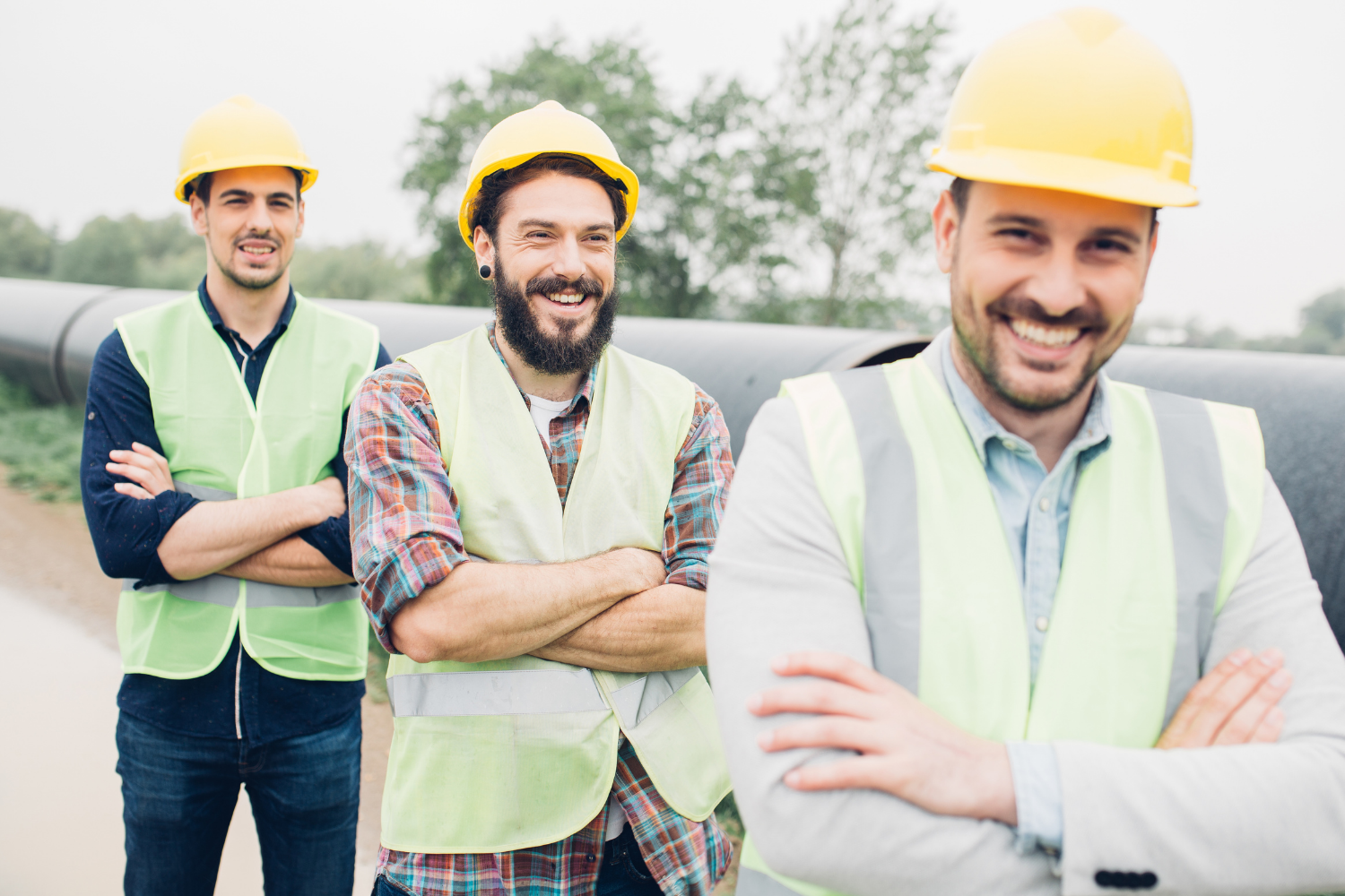 Photo of 3 happy men. They look to be part of a construction team with yellow hard hats and vests on