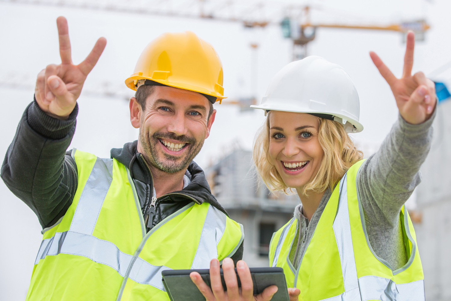 A male and female construction worker showing peace signs
