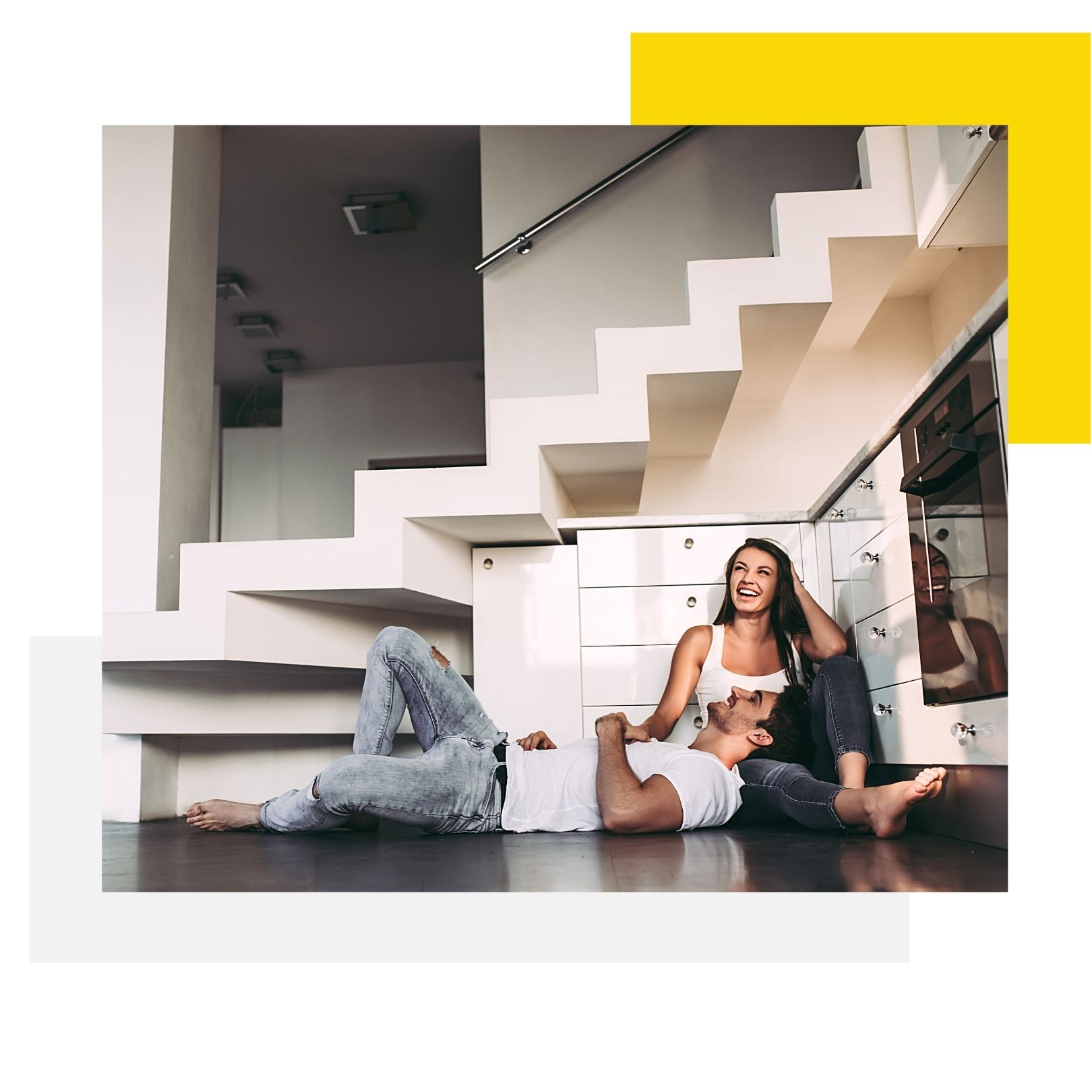 Young couple smiling happily as they sit on the floor of their new kitchen renovation.