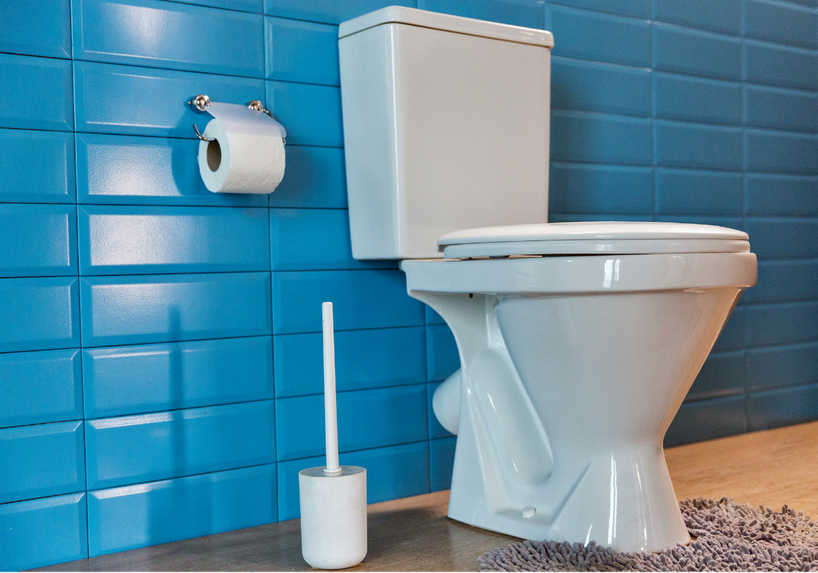 Toilet Renovation with a blue tiled wall and a while toilet